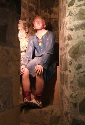 Depiction of a medieval toilet in Carrickfergus Castle. The mannequin on the toilet is King John.